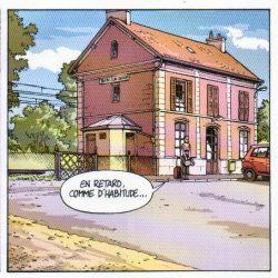 """La Gare     Petite gare avec un étage. La compagne du Chineur attend devant une valise à ses pieds et dit :""""En retard, comme d'habitude !"""""""